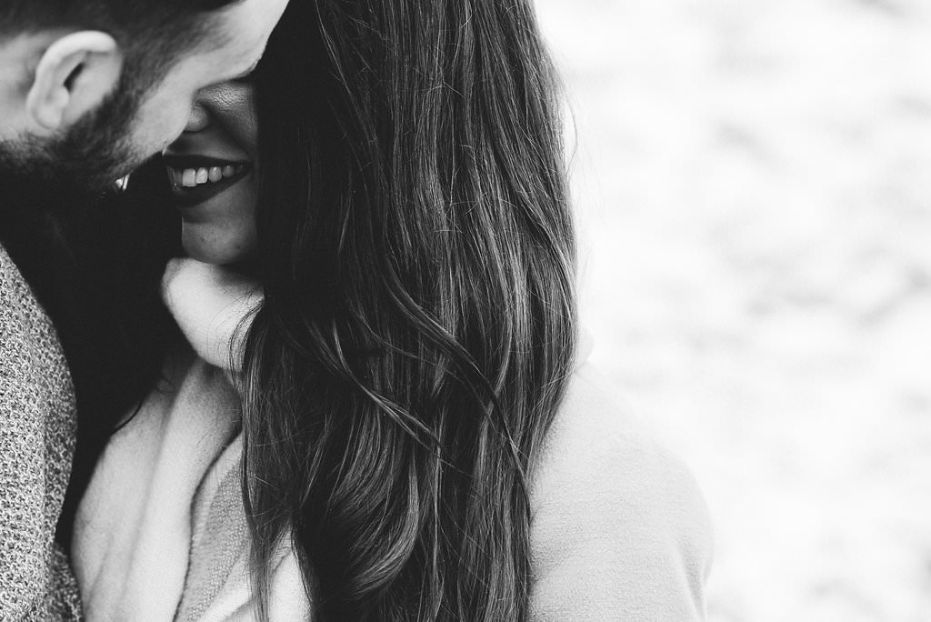 Intimate black and white portrait of couple kissing