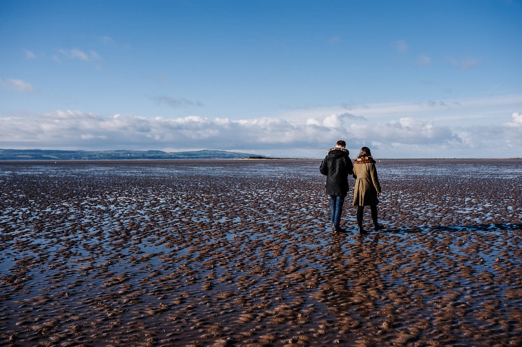 Couple walking along the beach at West Kirby