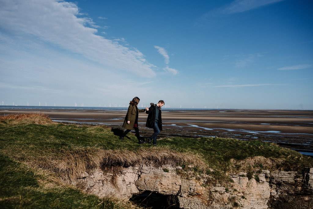 Natural shot of couple walking together on the cliffs at Hilbre Island. West Kirby Photography