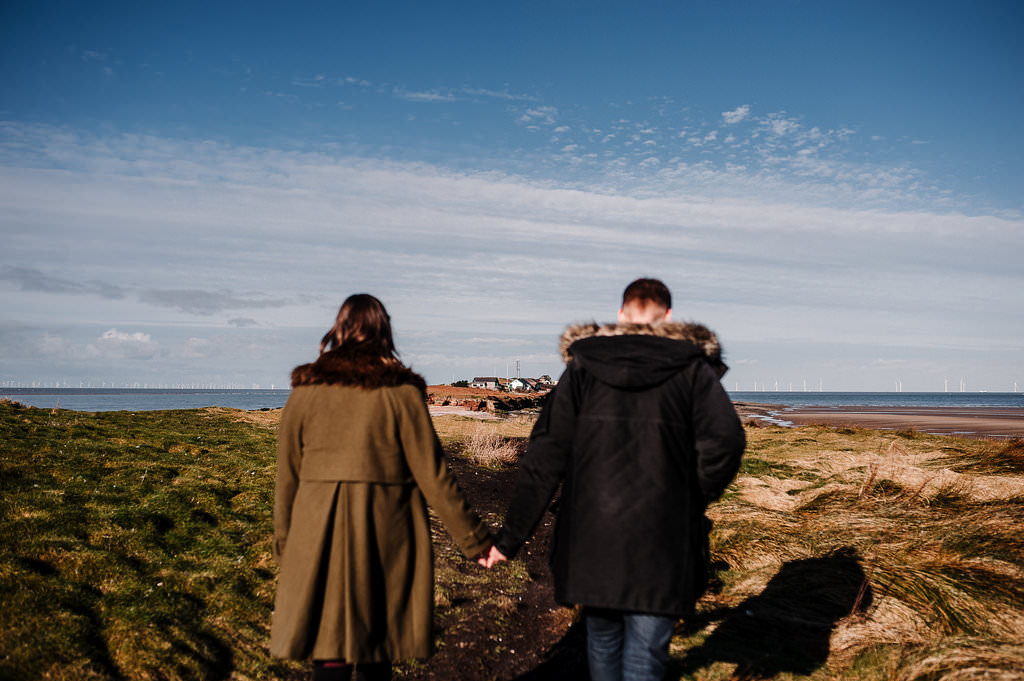 Natural photo of couple walking towards the Island in West Kirby