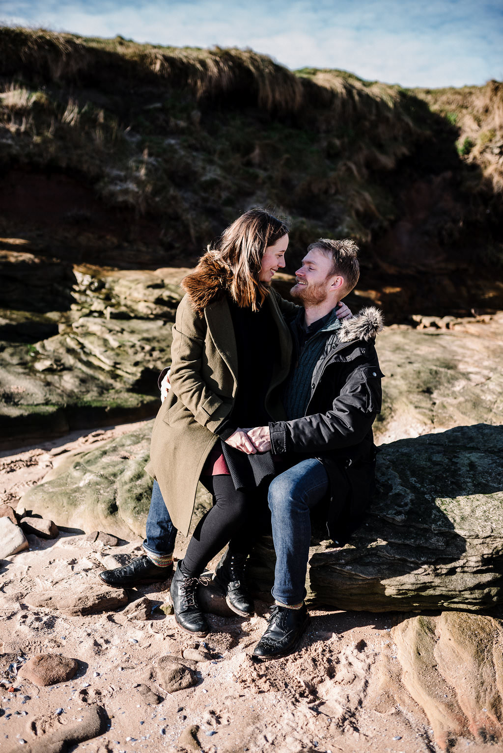 Intimate portrait of couple sat on rocks kissing. Engagement photography