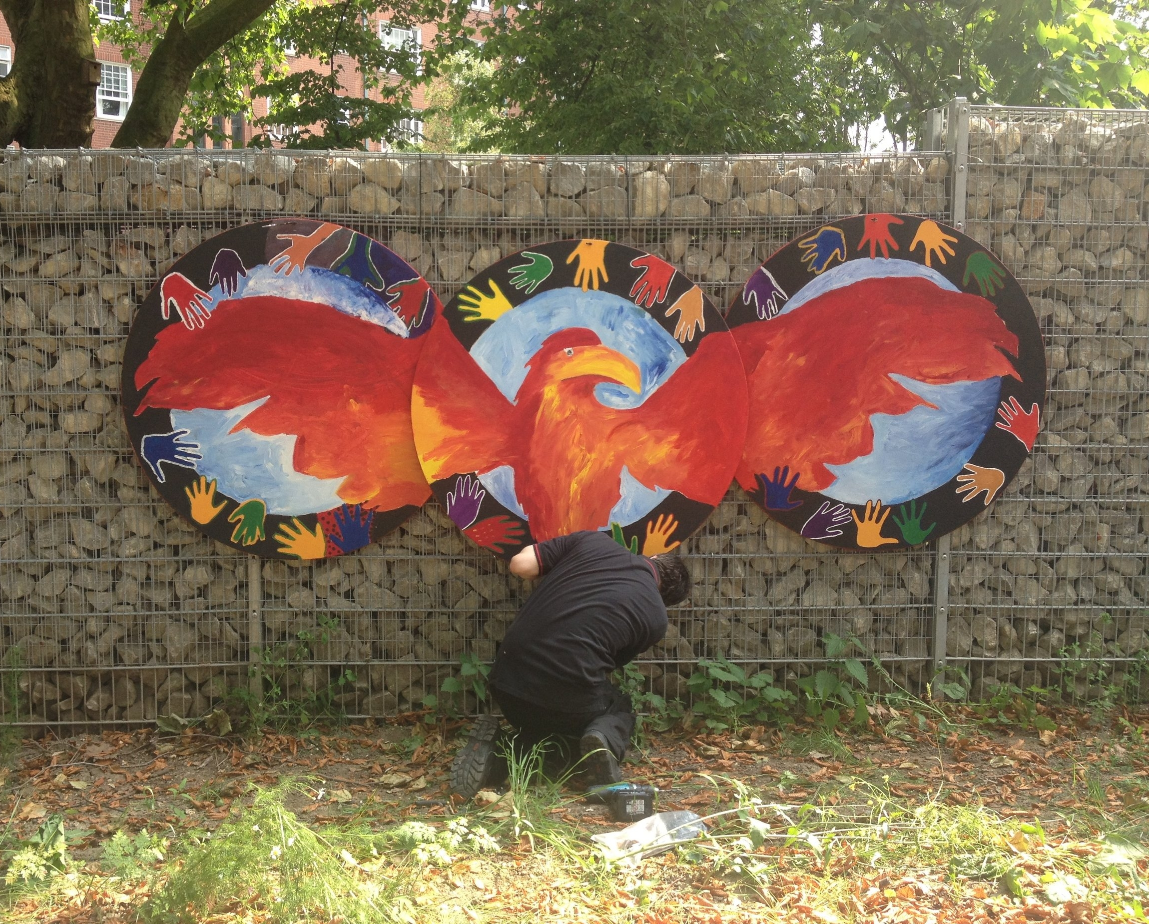 The Rise of the Phoenix - A one day workshop at Beachcroft School   The school wanted a bespoke design for their playground. Specifically, something to symbolise the rebirth and next chapter of their Year 11 leavers. I designed this 3 panelled phoenix which the students painted and and added their hands to. It now hangs in their playground.