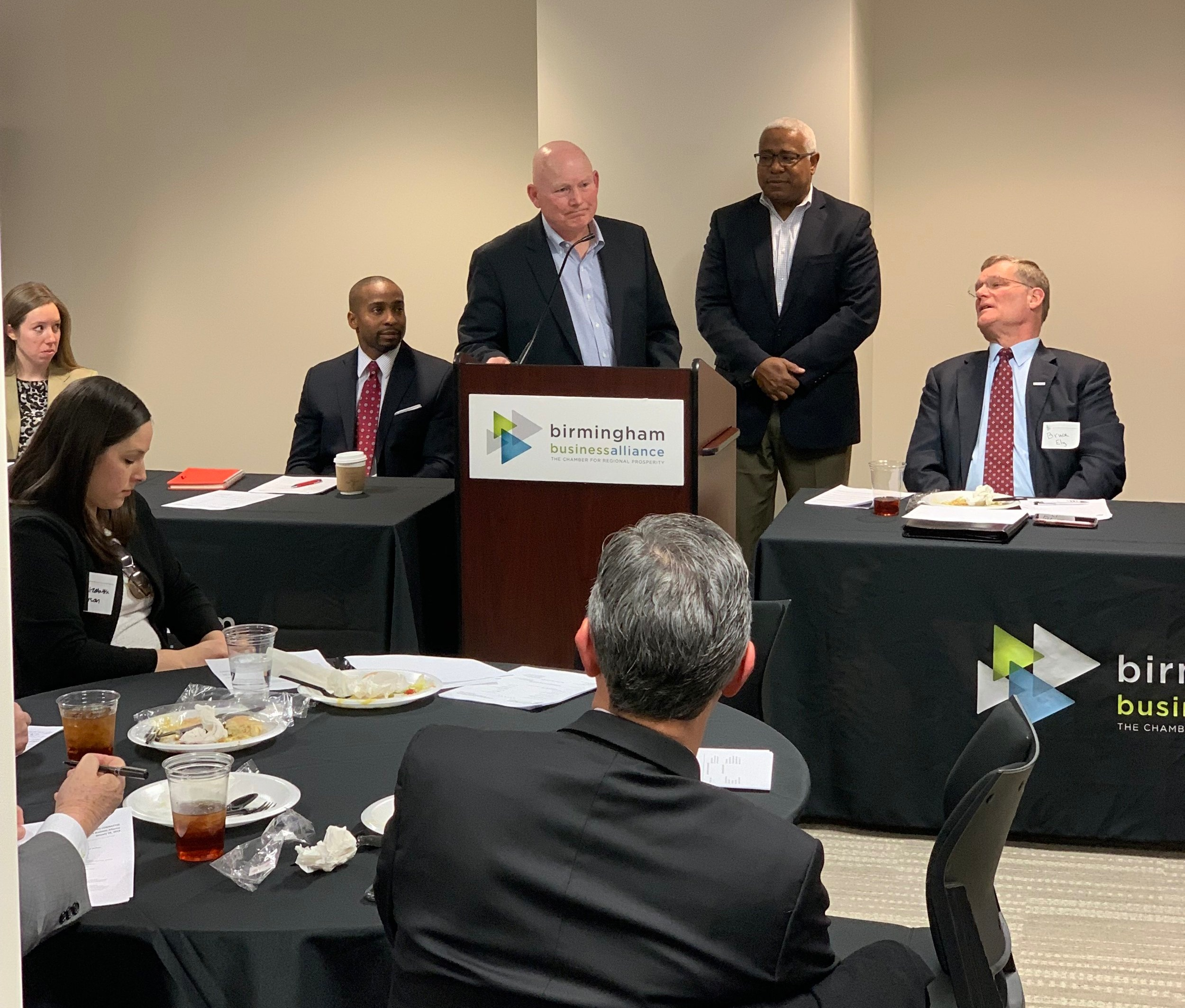 John Cooper, at podium, and DeJarvis Leonard, standing behind Cooper, addressed the Birmingham Business Alliance's Governmental Affairs Committee recently.