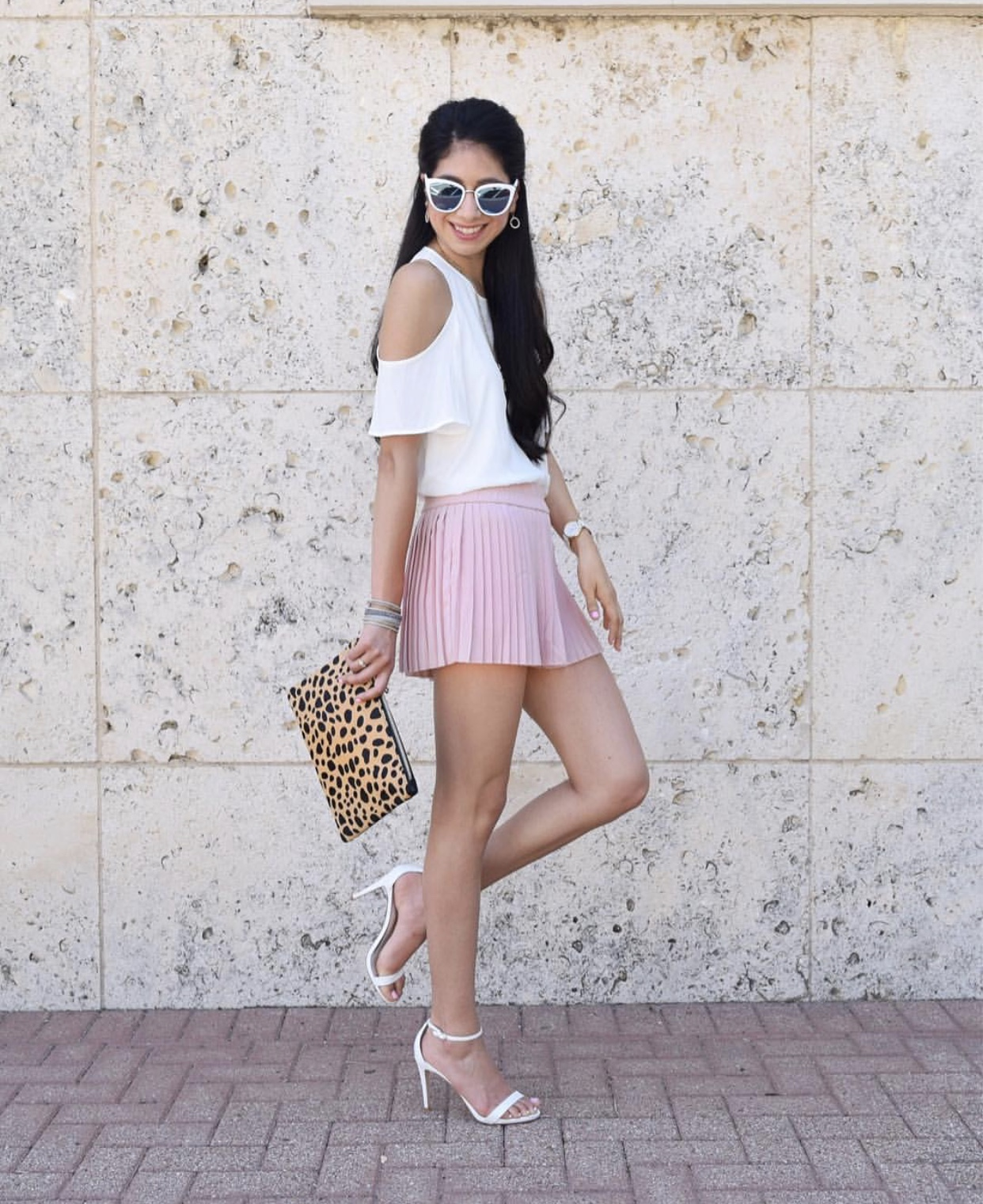 Screenshot from  @vanessaindallas  - Pleated shorts, clutch, white cold shoulder top