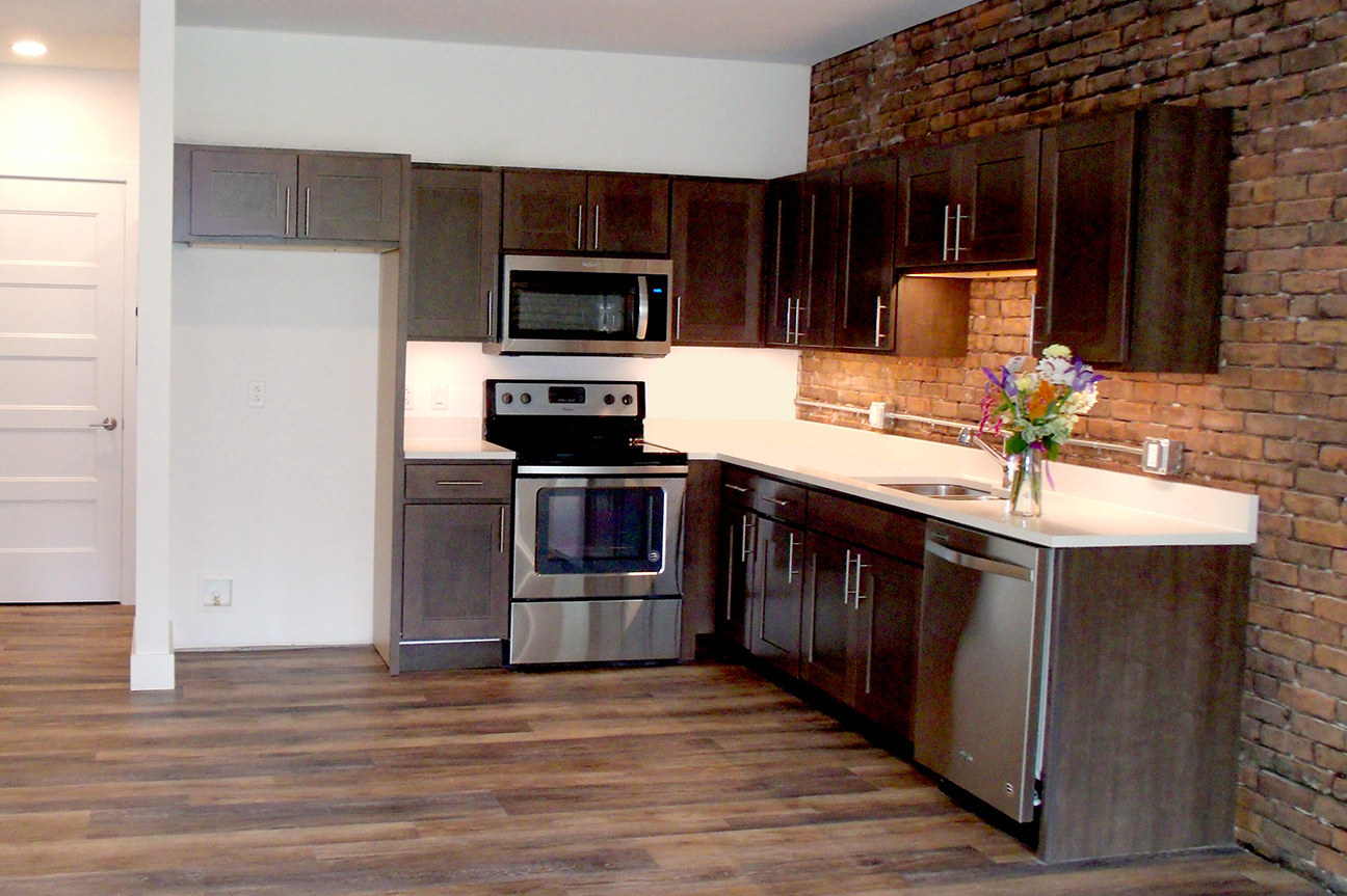 CONTEMPORARY KITCHENS  Stainless steel appliances, white prism quartz countertops, and deep slate-stained maple cabinets lend style and function. (Refrigerator not yet installed at time of photo.)  SEE MORE