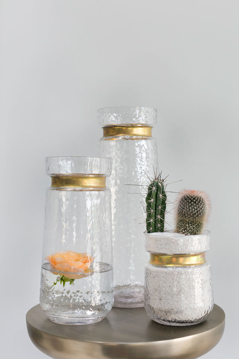 Jasmine Vase - Mouth blown clear glass vase with a cinched neck and a rich gold metal rim. Perfect for a simple centerpiece or a live succulent.