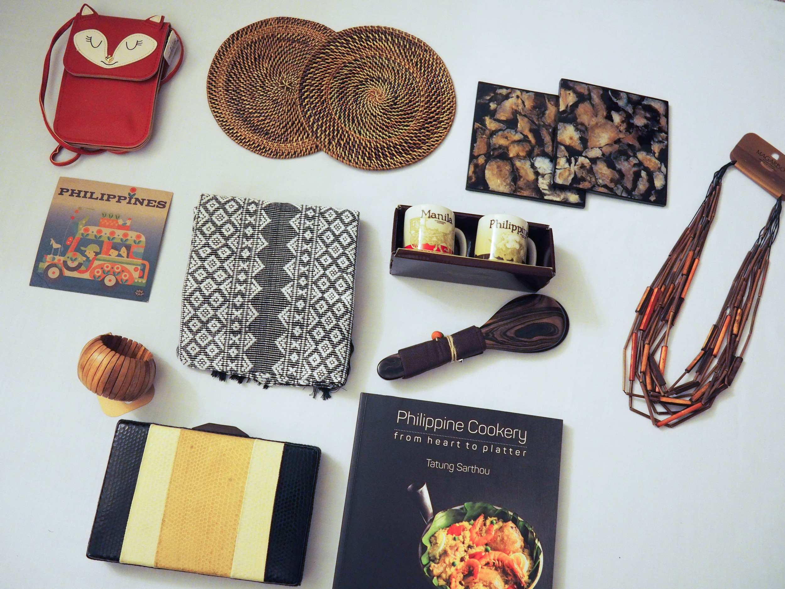 Philippine finds: Fox cell phone purse,woven trivets, capiz shell trivets, wooden necklace, local print, woven throw blanket, acacia wood spoon, doppio cups, wooden bracelet, snakeskin clutch, cookbook