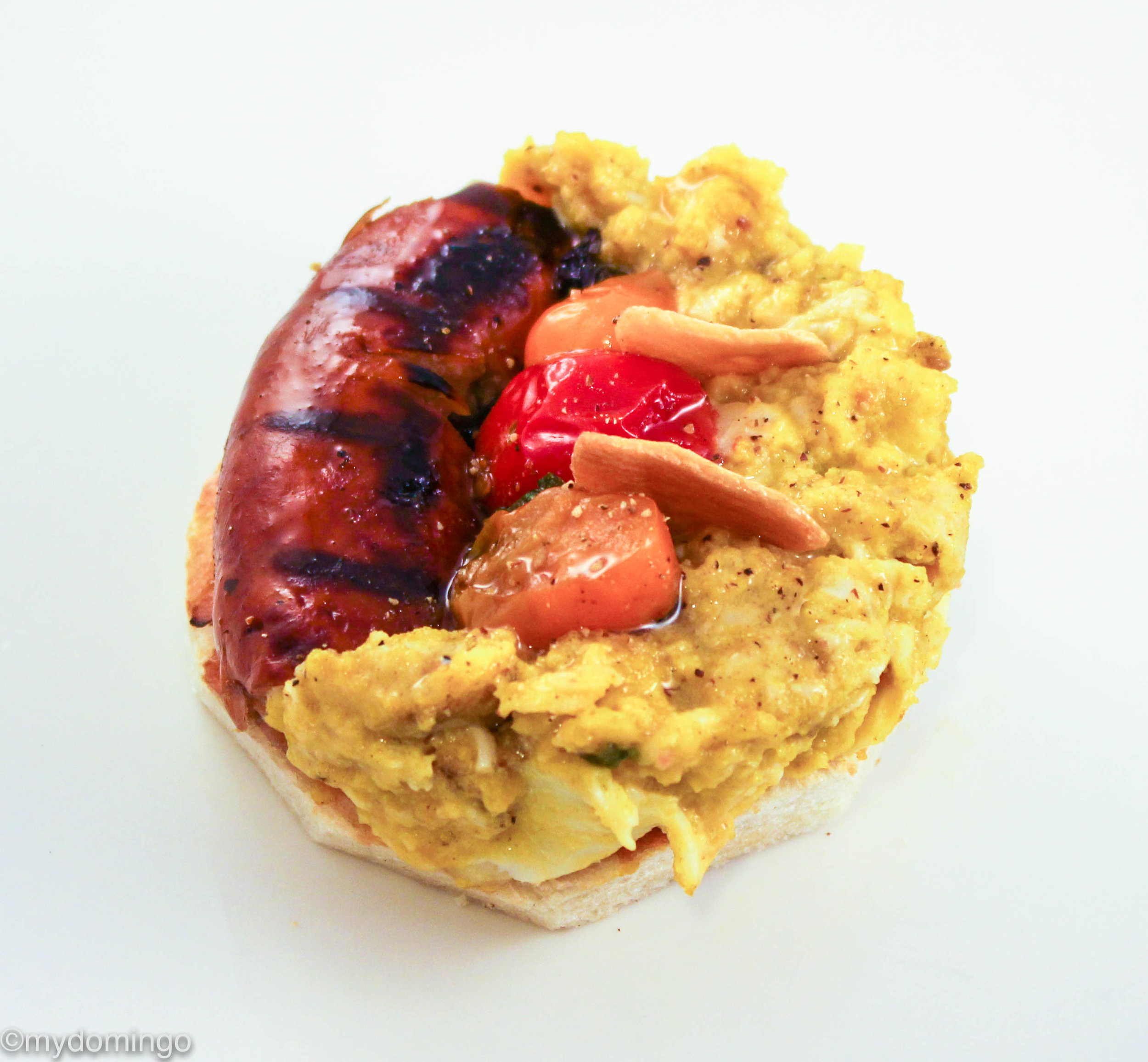 Open face four bite sandwich with turkey sausage, scrambled eggs, tomatoes, spinach, garlic crisps served on a sourdough bread.