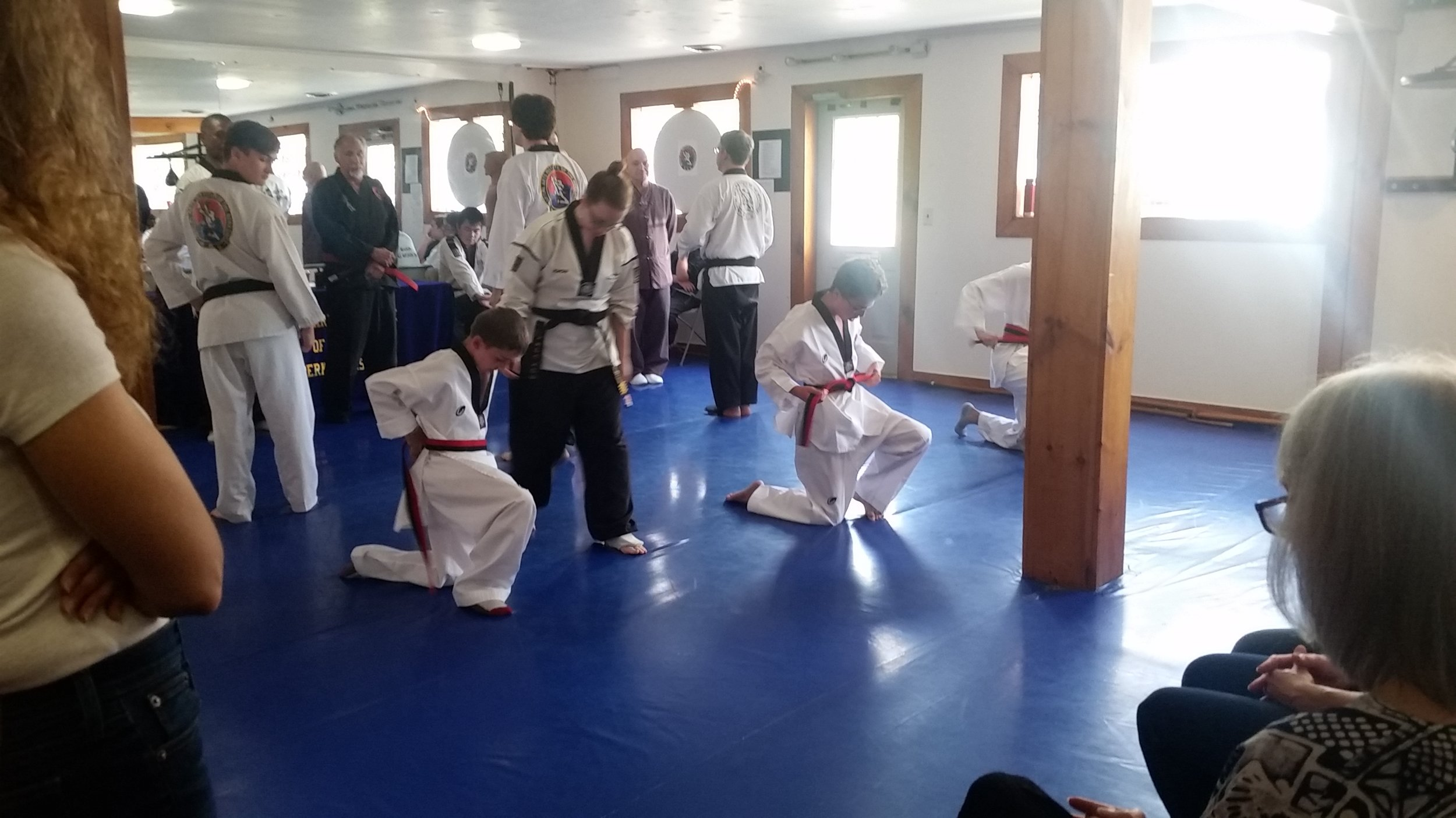 First Dan Candidates kneel to tie their belts at the beginning of the test.