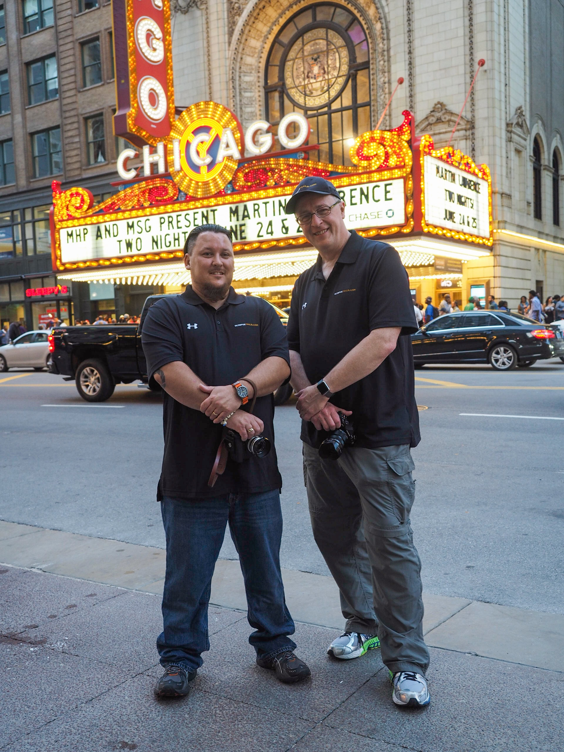 Jamie MacDonald and Mike Boening, Olympus Trailblazers, posing before the Chicago Theater.