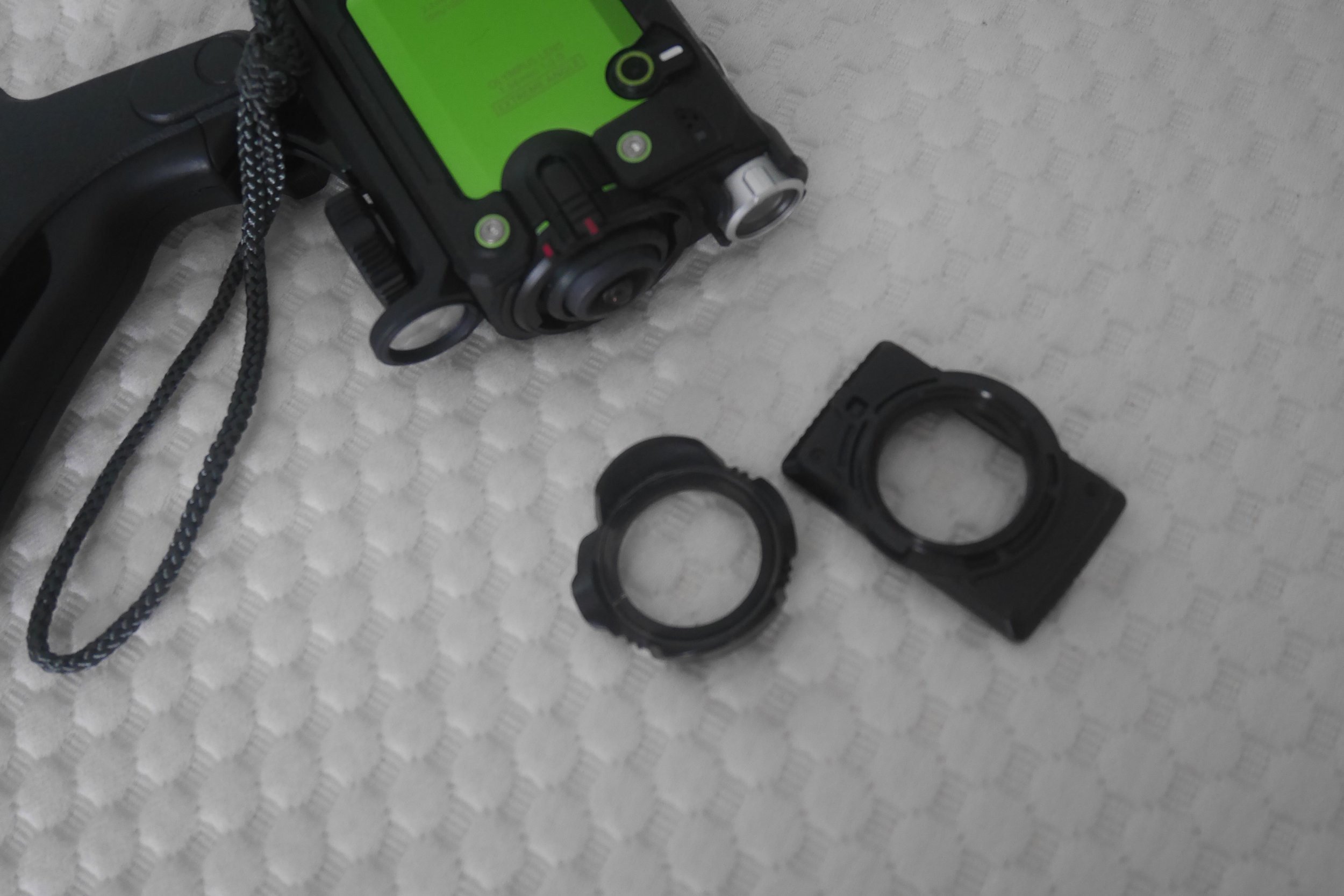 The Tracker's default lens protector and the rectangular protector for use underwater.