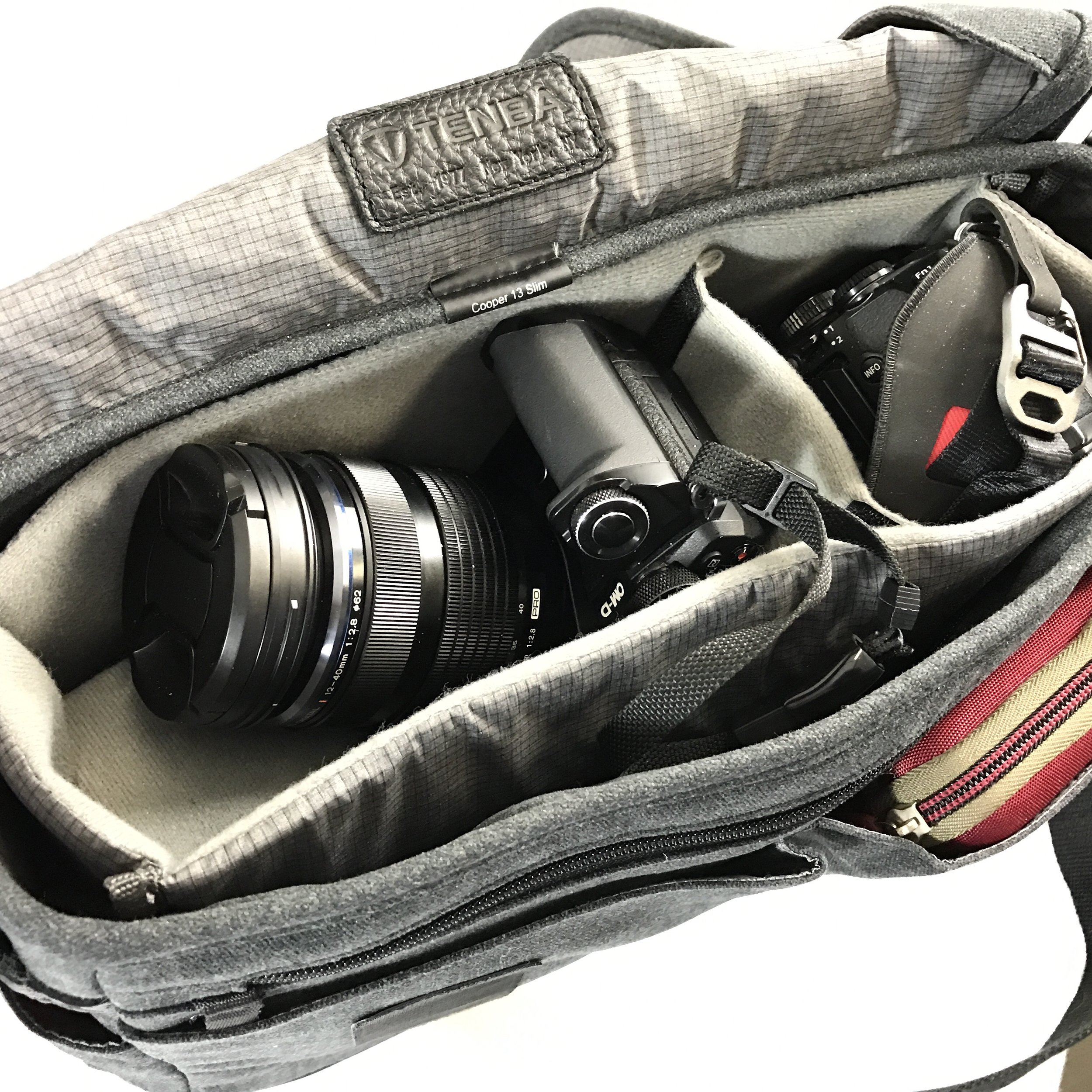 Showing how 12-40mm lens mounted on my E-M5 II rests nicely on soft divider that is on top of the TG Tracker and 12-32mm lens. Note red Case Logic bag in front expandable pocket.
