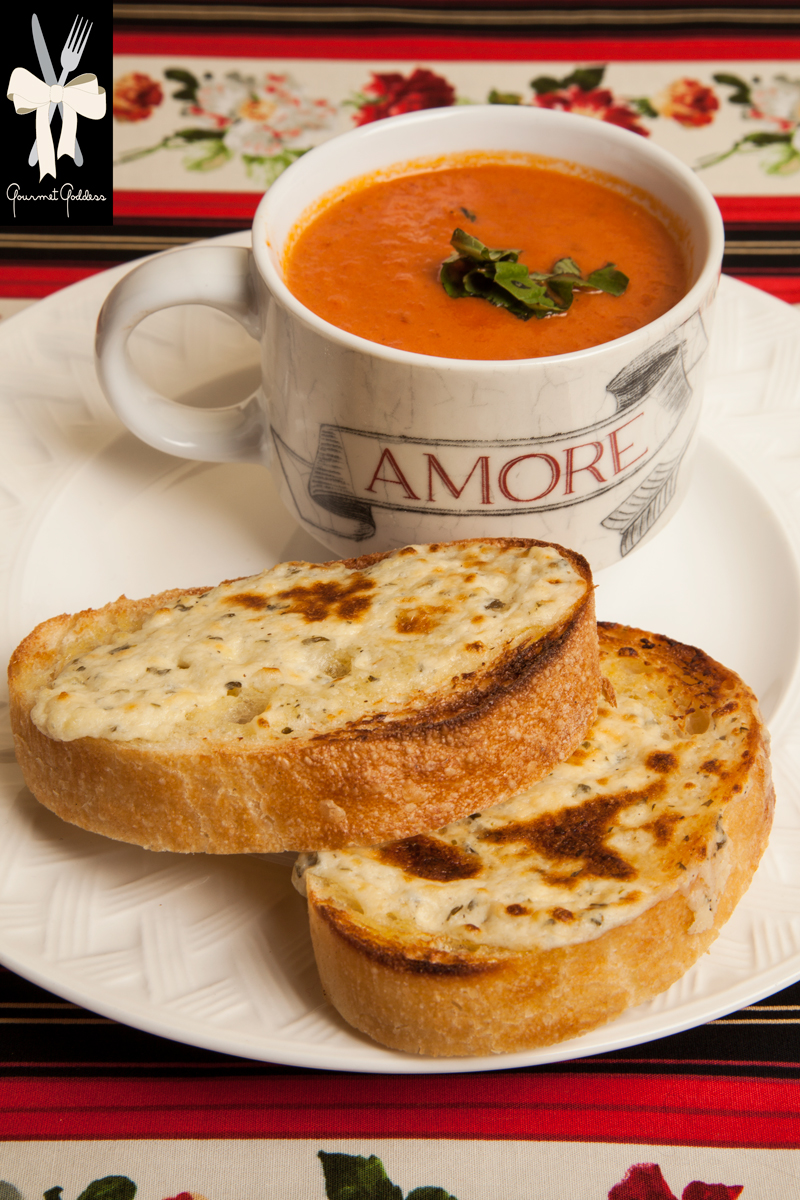 Italian Tomato Soup with Garlic and Herb Cheese Crostini  – now that's amore!    Oh baby it's cold outside so here's a recipe from The Gourmet Goddess that will warm and delight you.    During the winter, our thoughts turn to those things that keep us warm. Of course there are blankets and warm woolen mittens to ward off the chill, and if you ask the goddess, it is not an accident we celebrate love on Valentine's Day during one of the coldest months.    Then, of course, there are comfort foods which we turn to when the temperatures dip below freezing.    The Gourmet Goddess presents a savory low calorie tomato soup made Italian  style that says amore to anyone you make it for.          Ingredients  -  serves 8   2 tablespoons Olive Oil for Sautéing   2 tablespoons Butter   ¾ diced Sweet Onion   1 stalk Celery diced   1 Carrot diced   5 cloves chopped Garlic (plus 3 whole cloves to simmer in pot)   2 - 32oz. cans of Italian Tomatoes   ¼ cup Red Wine   1 can (½ cup) Tomato Paste   1 tablespoon sugar   1 teaspoon Dried Oregano   1 teaspoon Salt   ½ teaspoon Pepper   ¾ cup Heavy Cream   1 cup of Fresh Basil   Parmesan Shavings for garnish     Directions   Sauté onion, carrot and celery for 10 – 12 minutes.   Add chopped garlic and sauté 2 minutes.   Puree vegetables with tomatoes and return to pot. Add wine, tomato paste and seasonings and simmer for an hour.   Turn off and add cream to pot. Stir well.     Garlic Herb Crostini   Loaf of Olive Oil Ciabatta sprinkled with Sea Salt   6 ounces of soft garlic and herb cheeses   ½ cup grated parmesan cheese     Directions    Drizzle of olive oil, extra for brushing bread.  Line a cookie sheet with parchment paper.   Slice ciabatta in half inch slices. Brush bread with olive oil.   Mix cheese and olive oil and spread on bread.   Broil for 1 minute monitoring carefully.   Serve crostini floating on top of a bowl of soup   OR garnish a cup of soup with a chiffonade of fresh basil and parmesan shavings, crostini on the side.    -