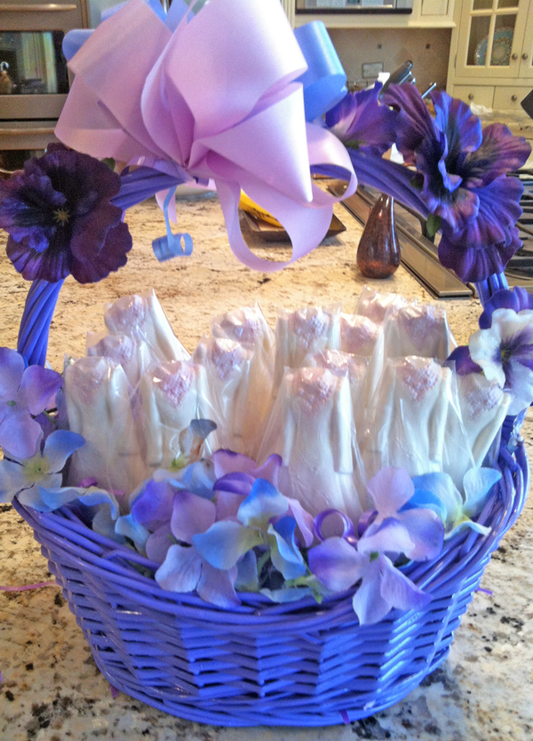 Shower Favors From The Chocolate Goddess          Here is a sweet and lovely favor for your guests to take home from a bridal shower/celebration. I displayed them in a lavender basket that uses flower petals rather than traditional grass, with flower petals glued onto the handle. Although I usually prefer real chocolate, I used vegetable oil based chocolate pieces because they can be obtained in a brighter white color than cocoa butter based ones.        What you need:   Bridal dress shaped molds, I used 2 and repeated the process over a few days   5 pounds of bright white chocolate pieces (I used Merken's) = 40 pops with the size of my molds   40 lollipop sticks   Luster dust and a fine brush, (I used lavender)   40 clear cellophane lollipop bags   A basket for display, lined with Styrofoam (flower petals to disguise styrofoam and decorate handle), add a bow!    Instructions:    Melt the chocolate discs in the microwave using a glass bowl. Make sure to heat the chocolate on 50% power and stir every 30 seconds. I used about a pound of chocolate at a time.   Then spoon chocolate into each cavity until full. Add lollipop stick making sure it is at least ¾ of an inch into pop. Tap several times to bang out air bubbles.   Refrigerate 30 minutes to harden. Carefully bend mold slightly to loosen pops and invert gently onto rack or cookie sheet.   After repeating process until you have the number of pops you need, brush on a tiny bit of edible luster dust on an embossed section (I did the floral neckline).   Put them in a clear cellophane bag; fasten/seal bye tying a coordinated ribbon, and display in basket.   A wedding favor fit for a goddess!   - Barbara Esatto, The Chocolate Goddess