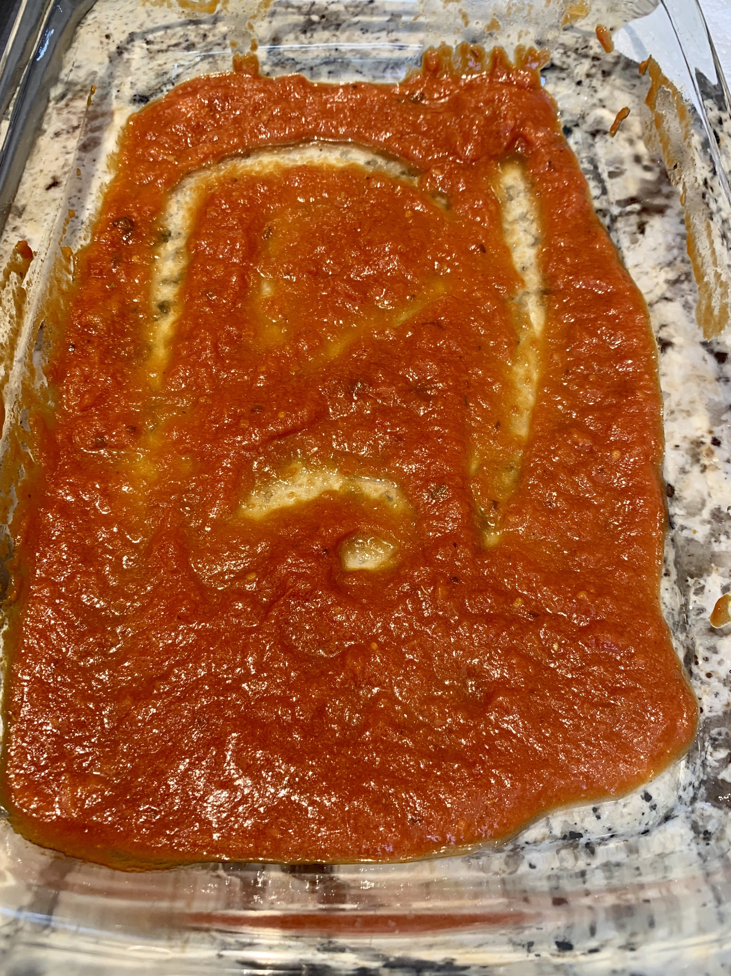 - Place a ladle of tomato sauce in bottom of 9 x 13 oven proof baking dish.