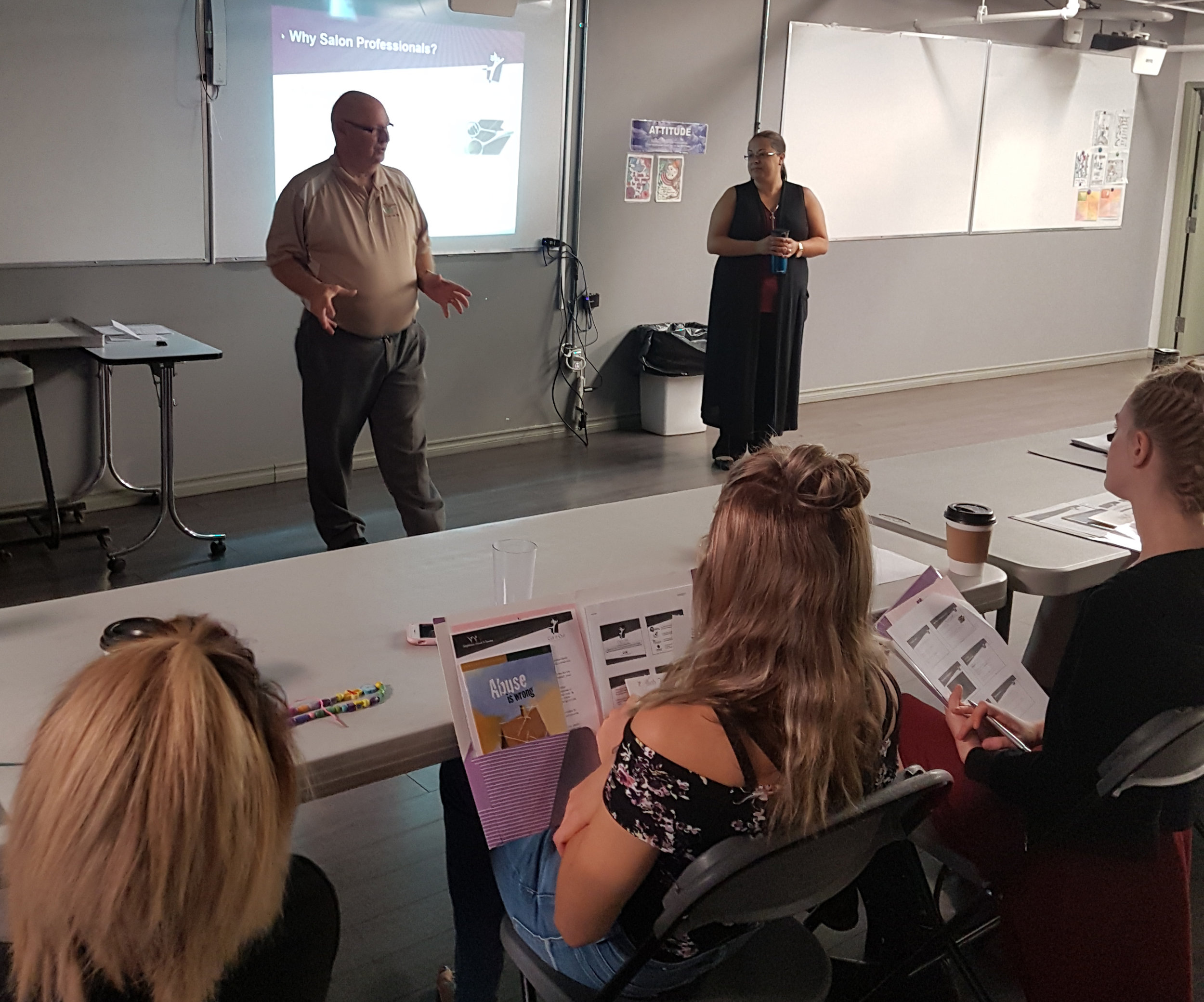 Perri Garvin, United Way and Jenn Vogel, Families First Society, speak to salon students about domestic violence awareness.