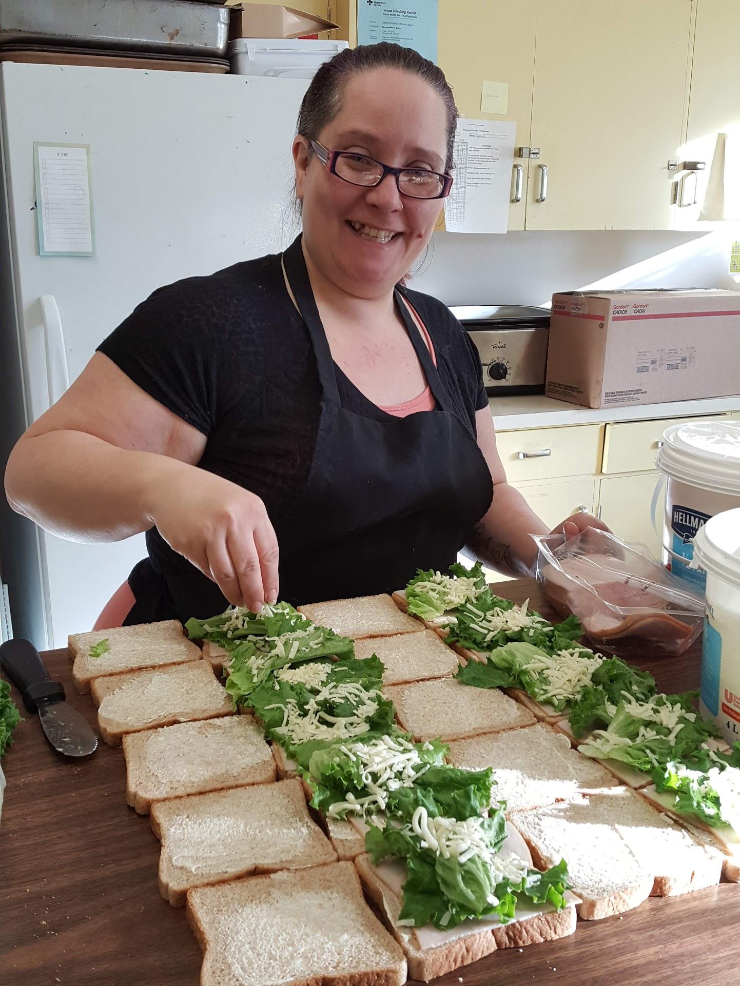 Tamara Kelly adding grated cheese to fresh turkey sandwiches