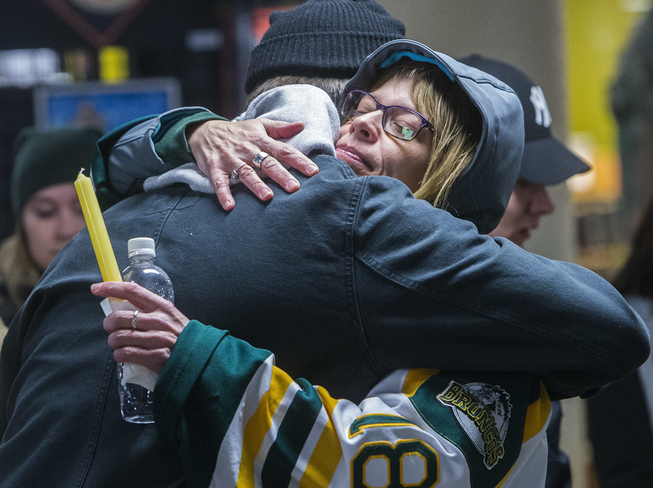 Shauna Nordstrom, the mother of Humboldt Broncos hockey player Logan Hunter, shares an embrace during a public vigil for her son and fellow Broncos teammates Conner Lukan, Jaxon Joseph and Stephen Wack who were all killed last Friday when the team's bus collided with a tractor trailer at an intersection near Tidsdale, Saskatchewan.  Photo credit: CHRIS COLBOURNE/St. Albert Gazette