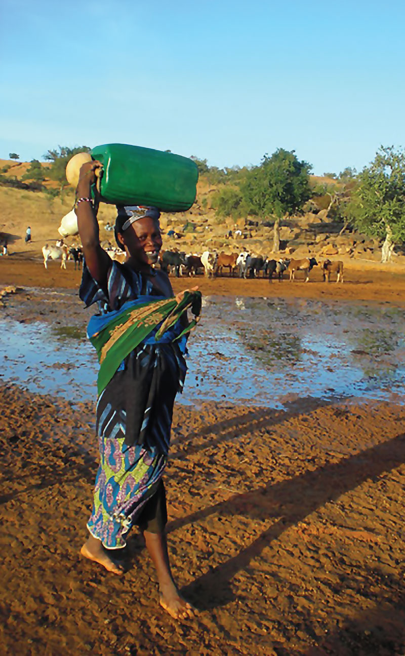 A Fulani woman at a spring carries water back to her village in Mali, West Africa. Photo courtesy of the Peace Corps.