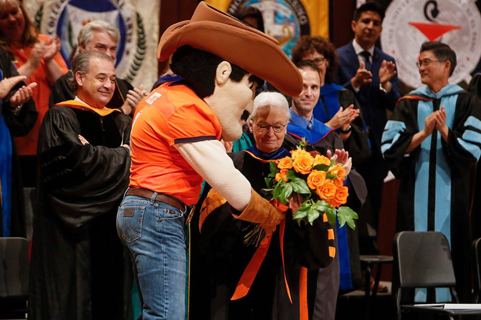 Paydirt Pete surprised UTEP President Diana Natalicio with a bouquet of orange roses at the 2018 Fall Convocation on Oct. 11,2018.  Photo by J.R. Hernandez / UTEP Communications