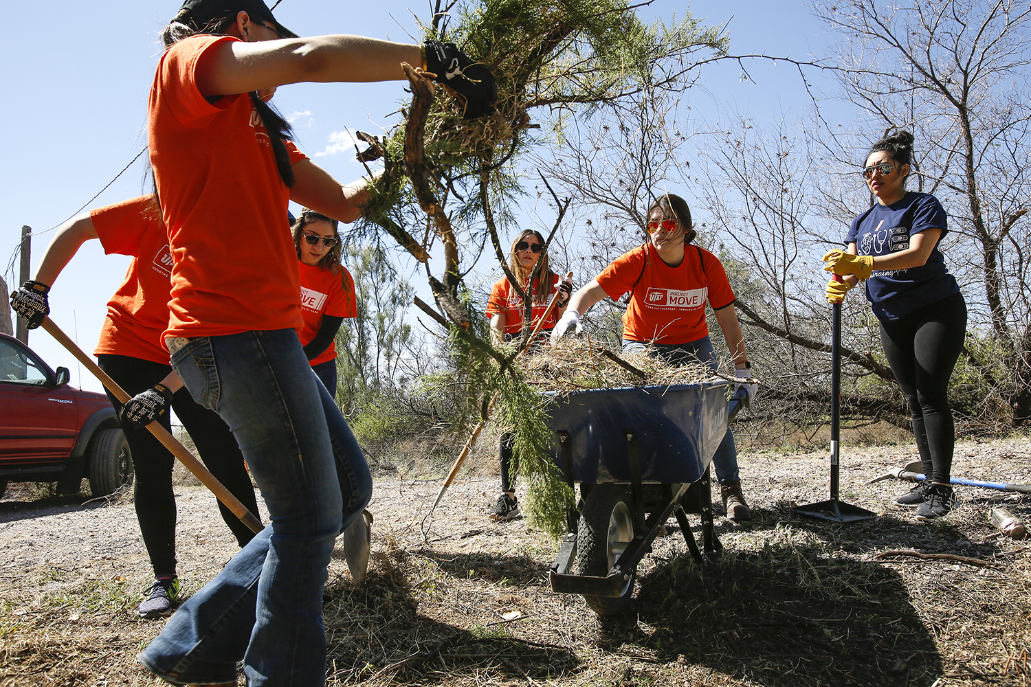 Volunteers help clear brush at a home that was among the many Rebuilding Together El Paso projects that also involved exterior and interior painting.