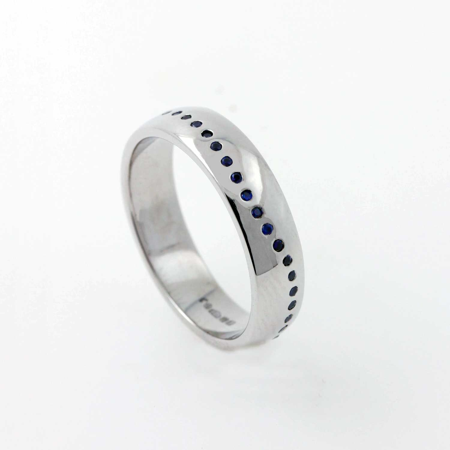 """Baby Blue - Sarah wanted to create a pinky ring for her husband Richard's special birthday to match his watch. I created a platinum oval band, with blue sapphires set in a wave pattern all the way around.""""Rich loves it, thanks so much"""" - Sarah Holden."""