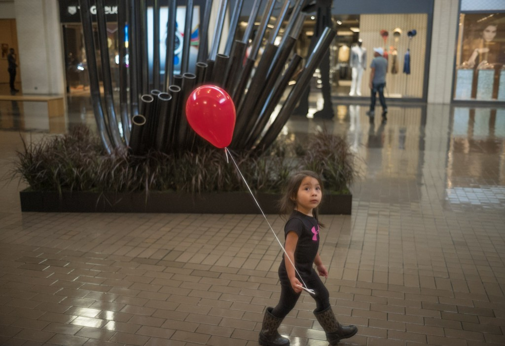 A young shopper enjoys Sebastien Leon's Diffracted Symphony at NorthPark Center © NorthPark Center