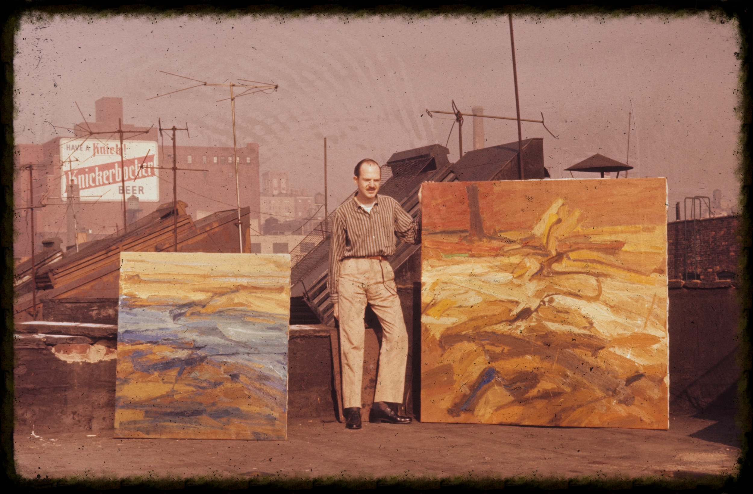 Jim Harvey with two paintings in NYC circa 1960. Photo courtesy of Bill Harvey.