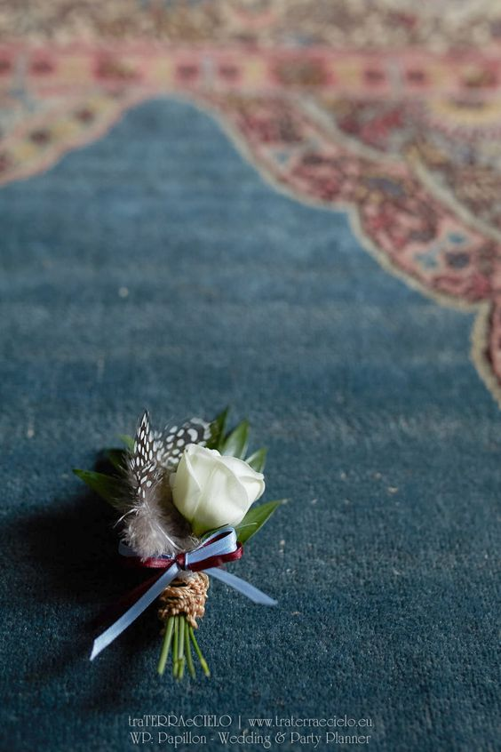 Groom's boutonniere - Will have duck feather and greenery with a white flower. Instead of it being wrapped in ribbon it will be encased in a bullet casing.
