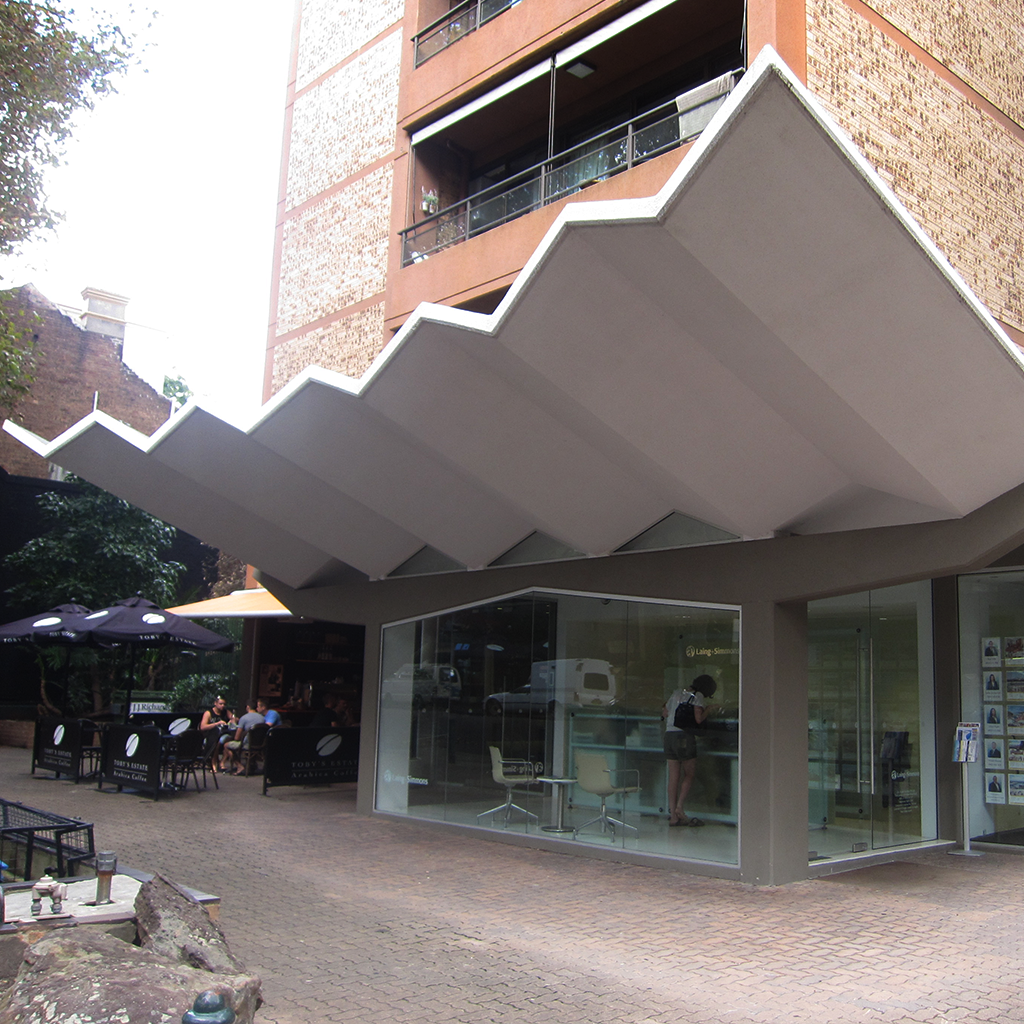 Small businesses, in the base of apartment towers, need to find unique ways to make themselves visible. In this example from Sydney a bold canopy marks the store front.    Sydney, Australia