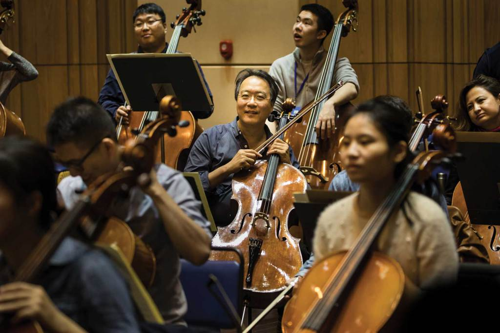 Yo-Yo Ma sits in the back of the cello section during orchestra rehearsal at YMCG. Photo by Li Lewei
