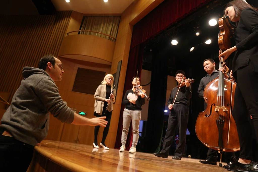 """Cellist Mike Block coaches a chamber group before a YMCG """"Tomorrow Concert."""" Photo by Liang Yan"""