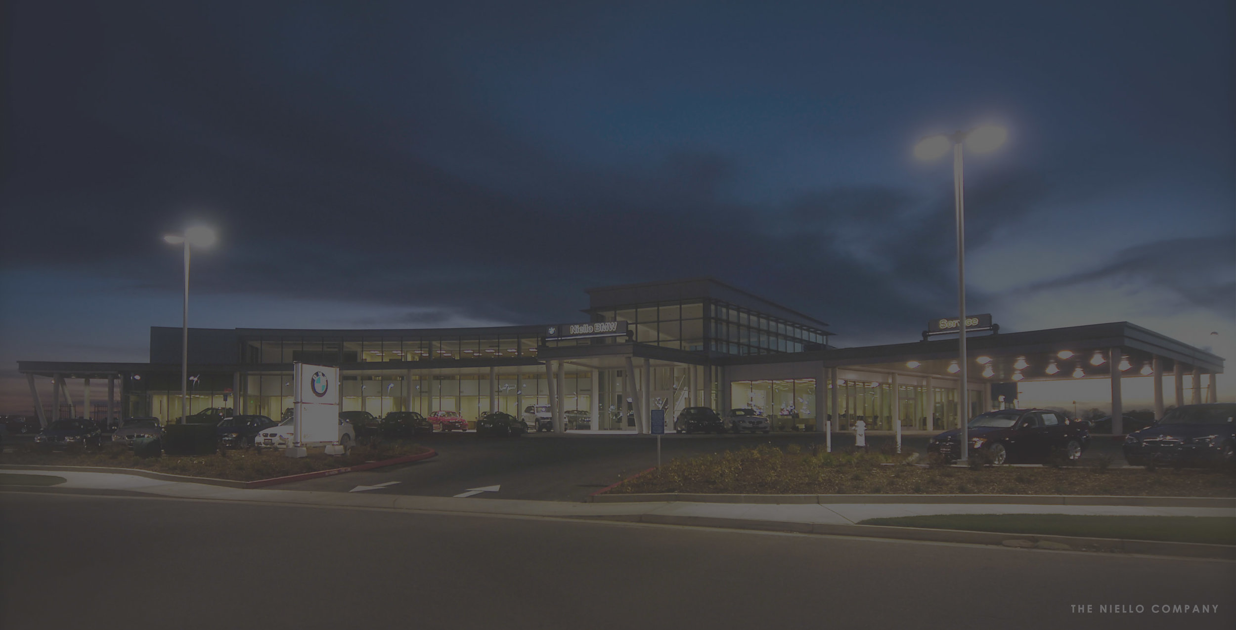 """A new BMW facility in Elk Grove, California reflects the premium quality and elegance of the BMW vehicle design. With a total building area of 53,900 sq. ft., the curved exterior façade of the showroom and uniquely shaped, tower element are composed of an aluminum curtain wall system with high performance, energy efficient glazing for maximum visibility and a """"lightness"""" to the building."""