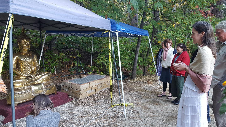 Mountain Stream Teacher Heather Sundberg and others contemplate the new Buddha