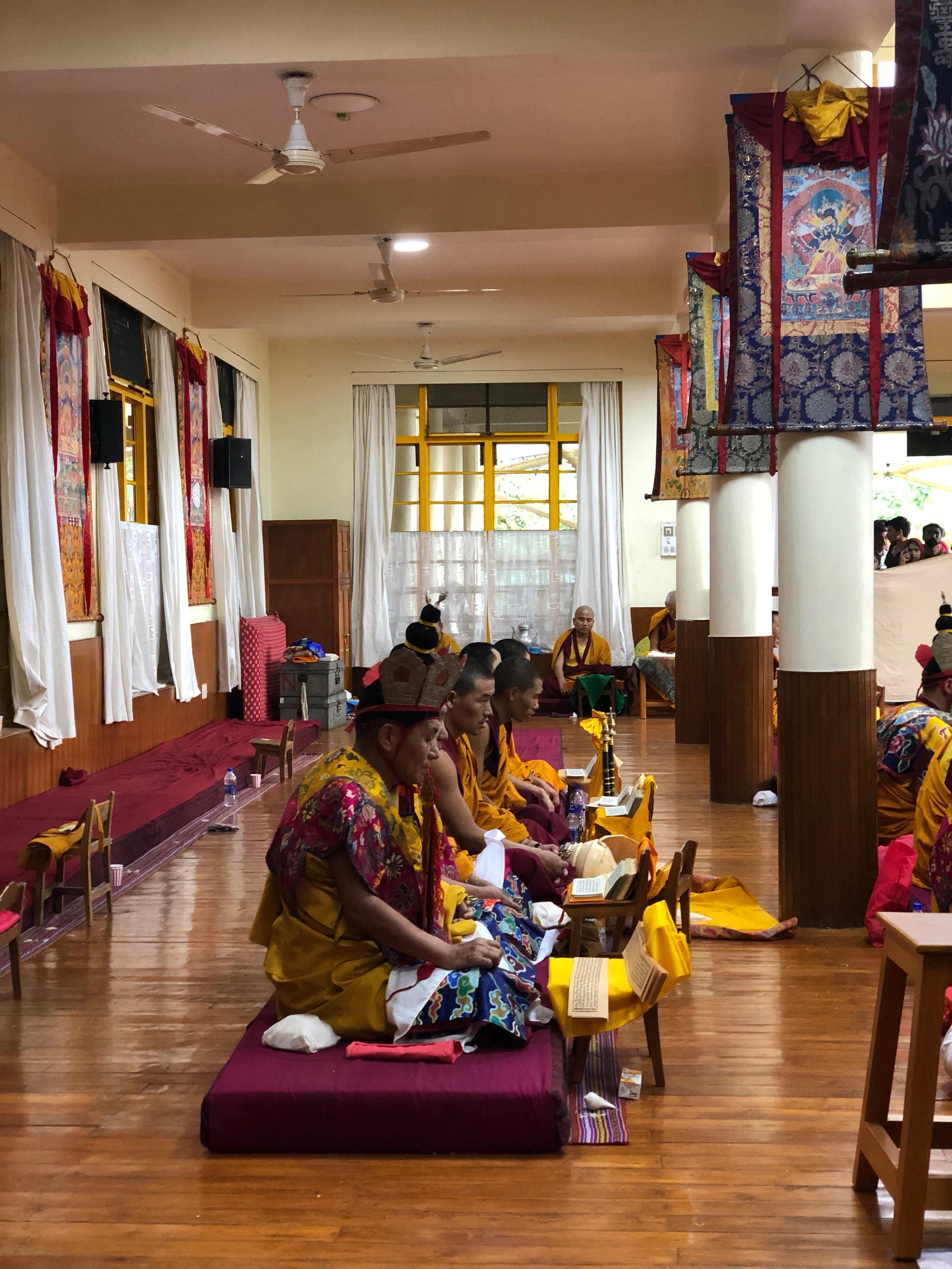 MONKS PRAYING AT THE DALAI LAMA MONASTERY