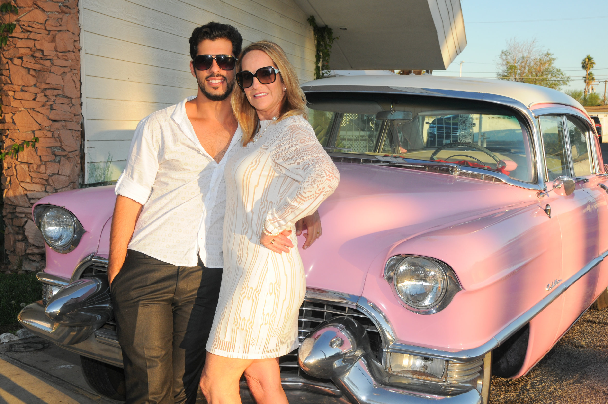 Couple posing in front of Pink Caddy