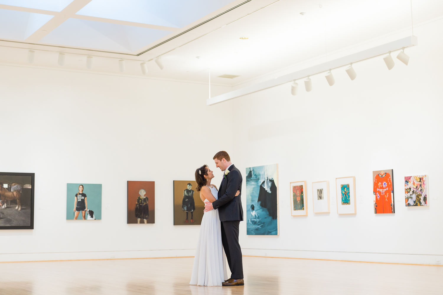 Bride and groom in an art gallery with paintings