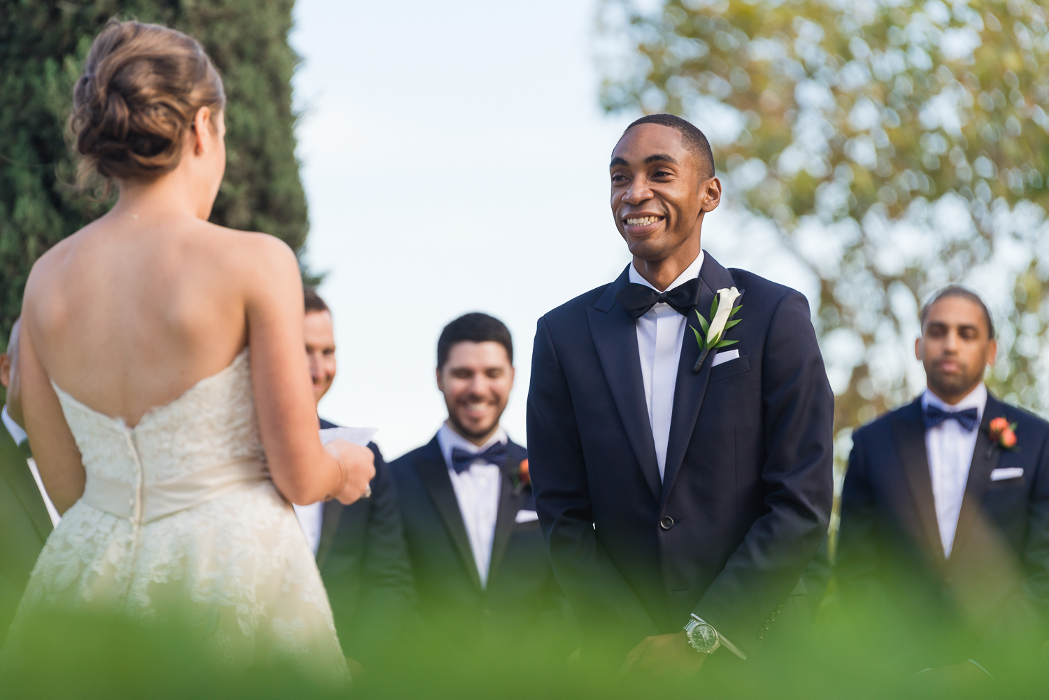 Groom laughing at bride's vows during wedding ceremony