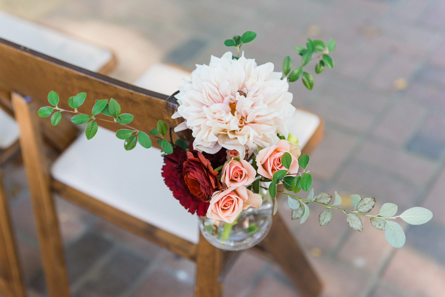 Pink and magenta wedding ceremony flowers affixed to a chair
