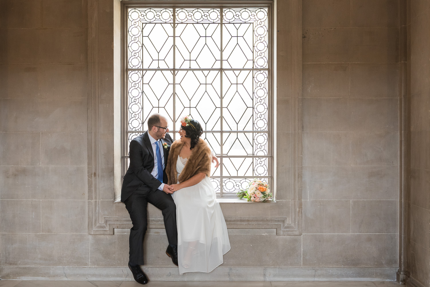 Bride and groom in windowsill at city hall