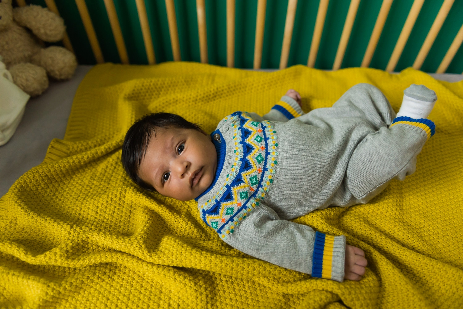 Baby in embroidered onesie laying on a yellow blanket