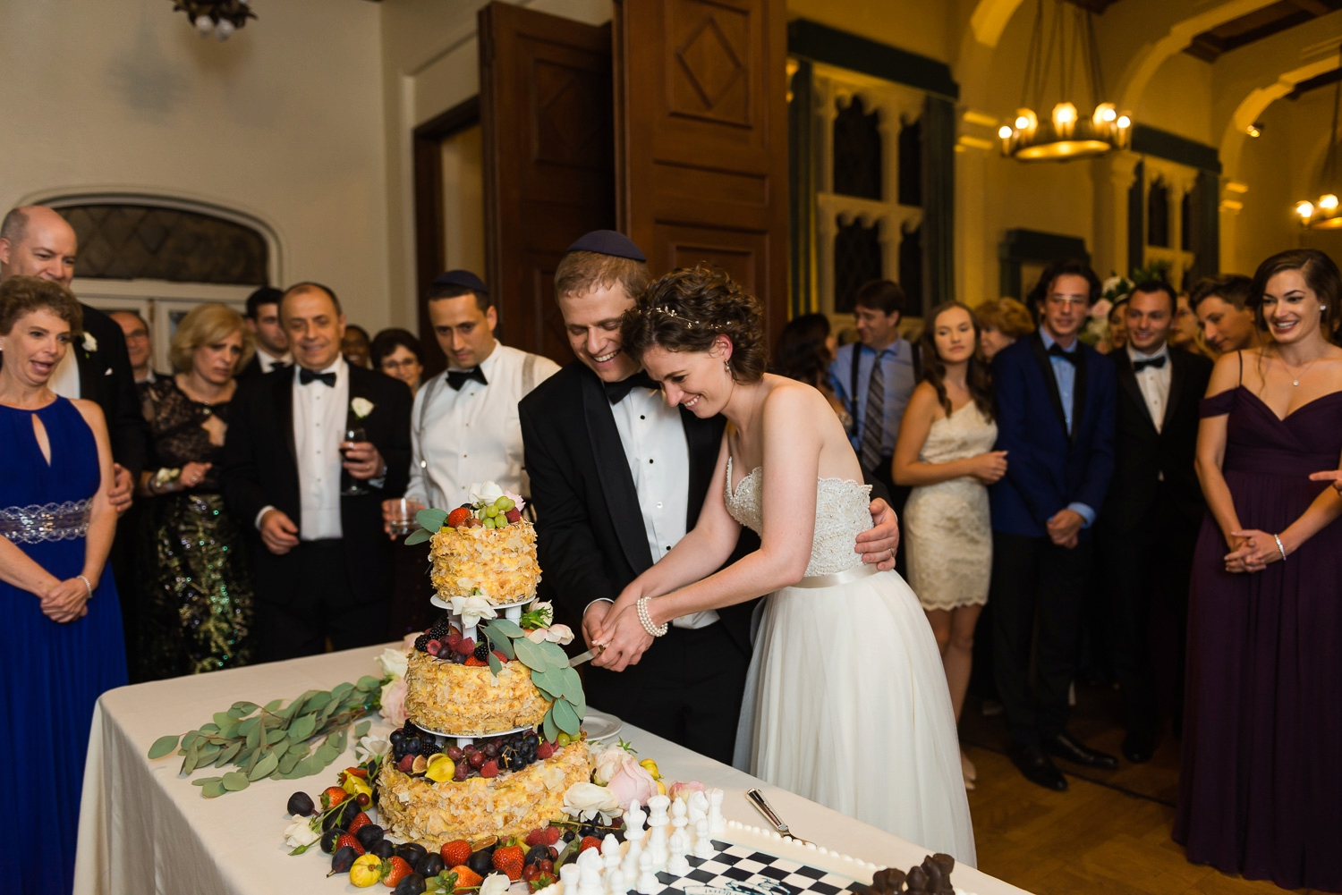 Bride and groom laughing as they cut the cake