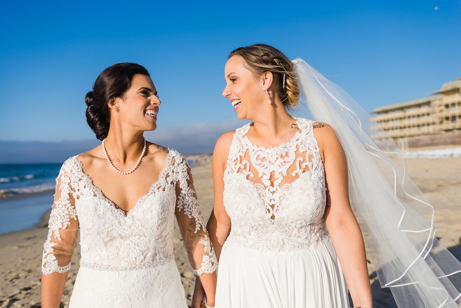 Two brides smiling at the beach