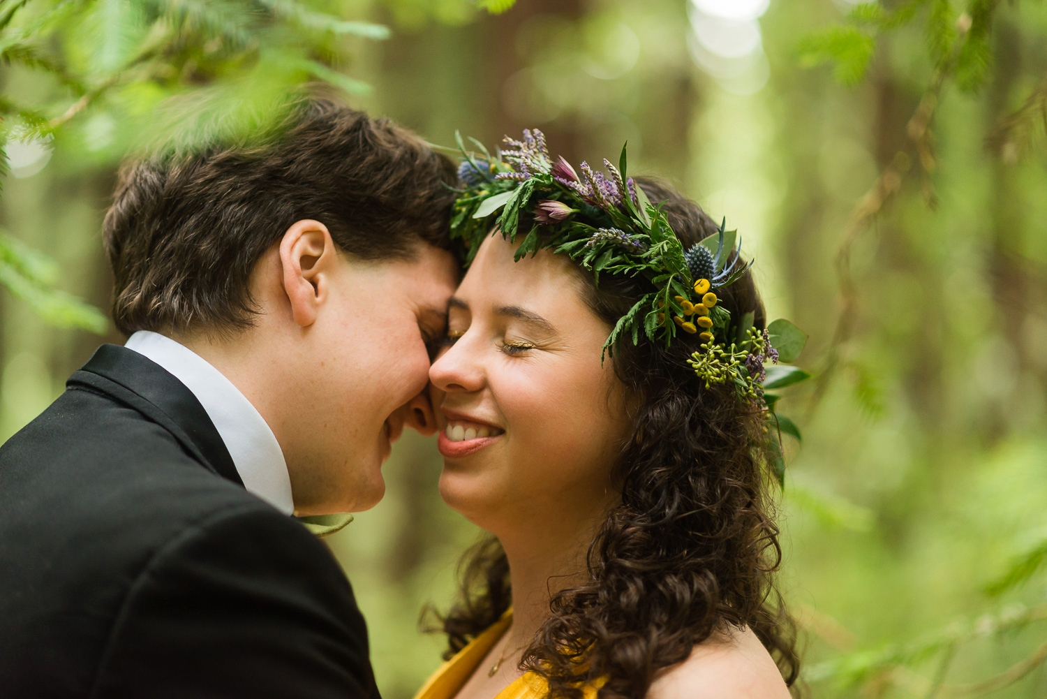 Bride and groom smiling under a tree