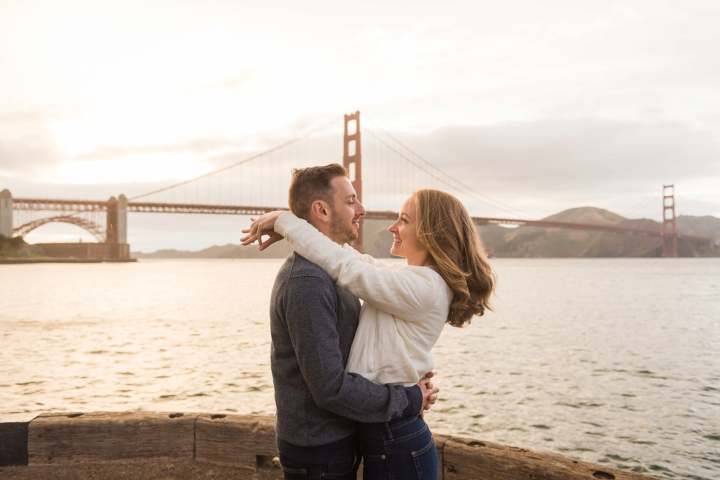 Couple laughing in front of the Golden Gate Bridge