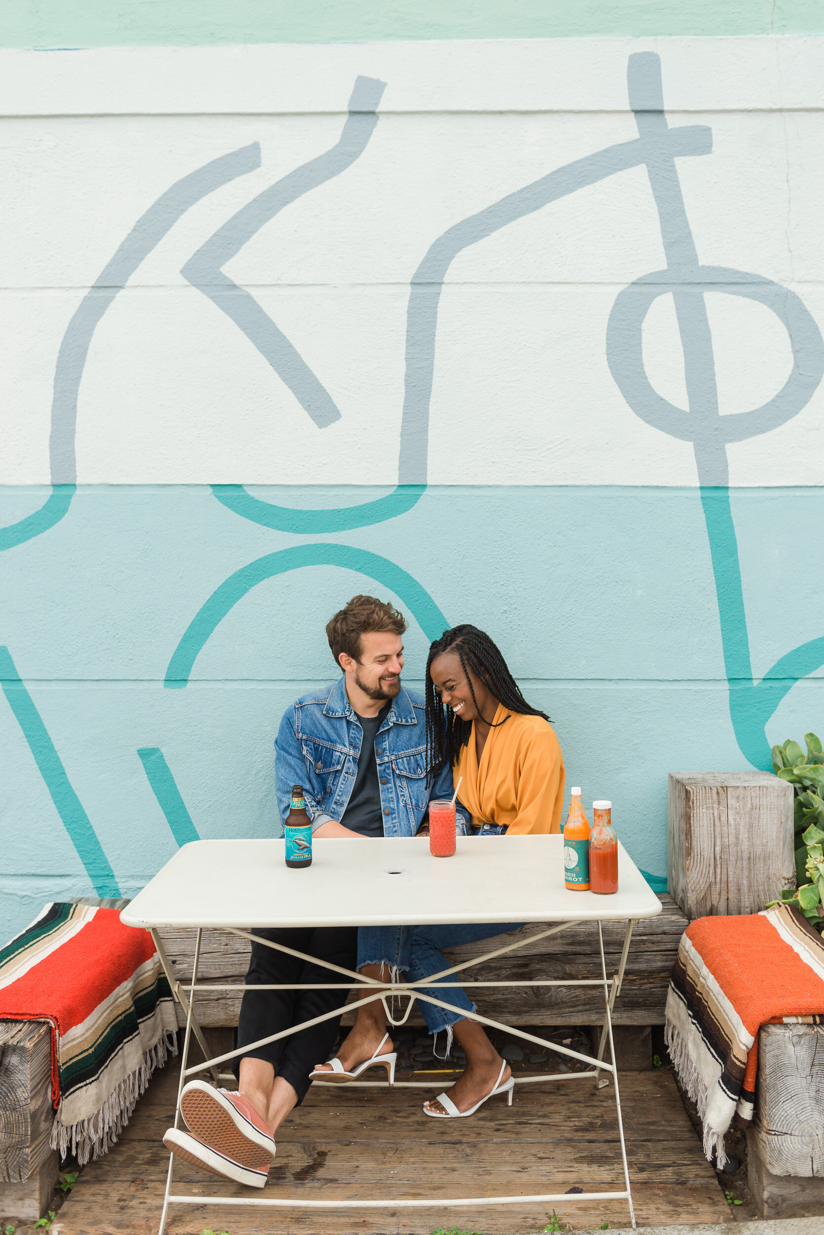 Engaged couple laughing in front of a blue mural in San Francisco