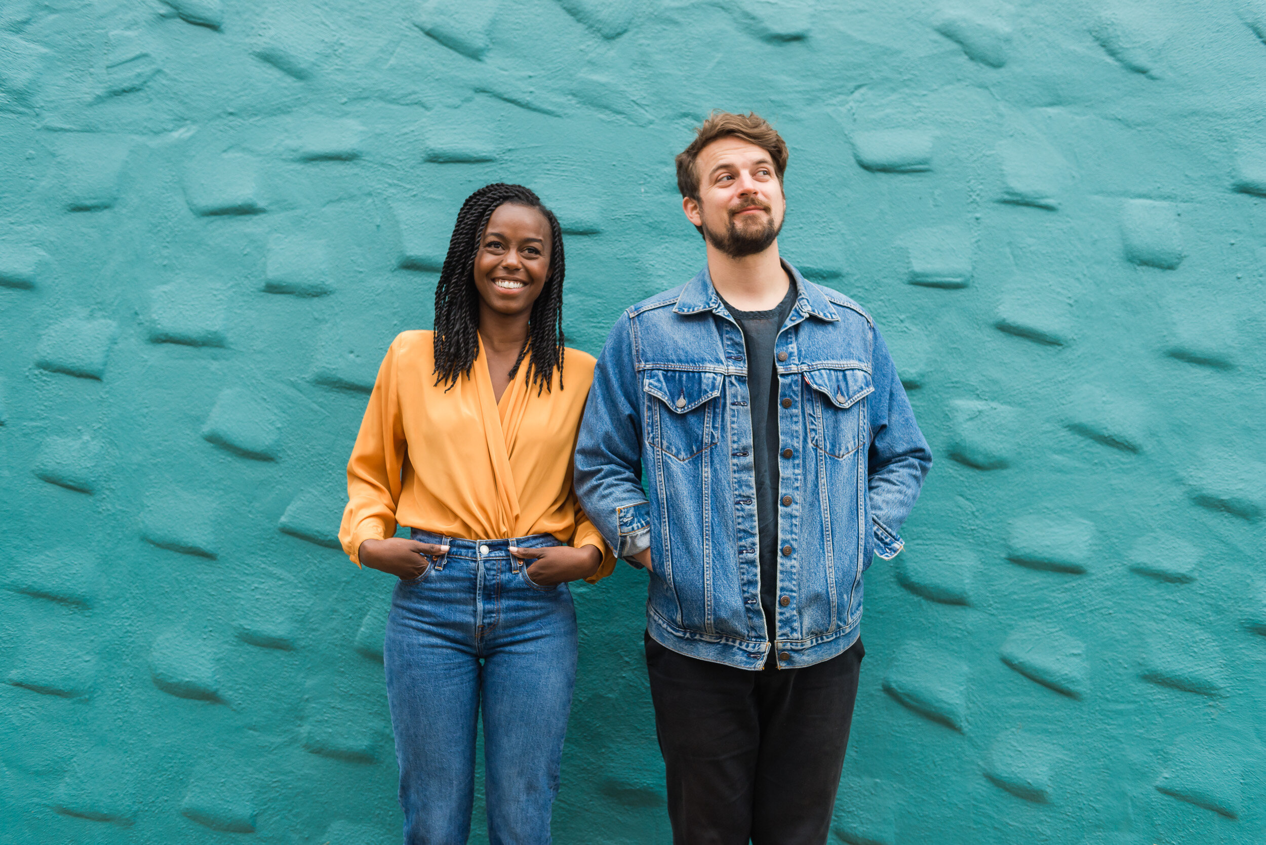 Engaged couple wearing Levis jeans and jack pose in front of a colorful house