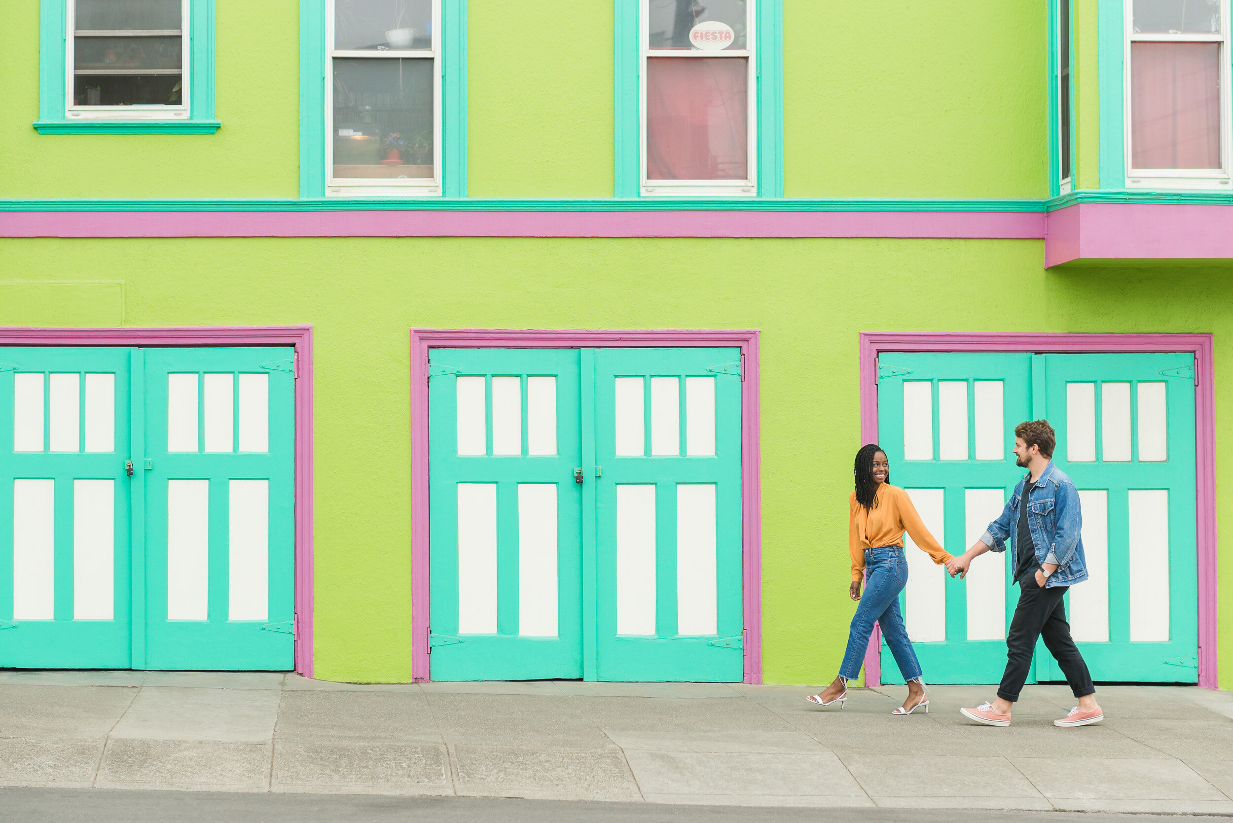 Engaged couple walking in front of a green house in San Francisco