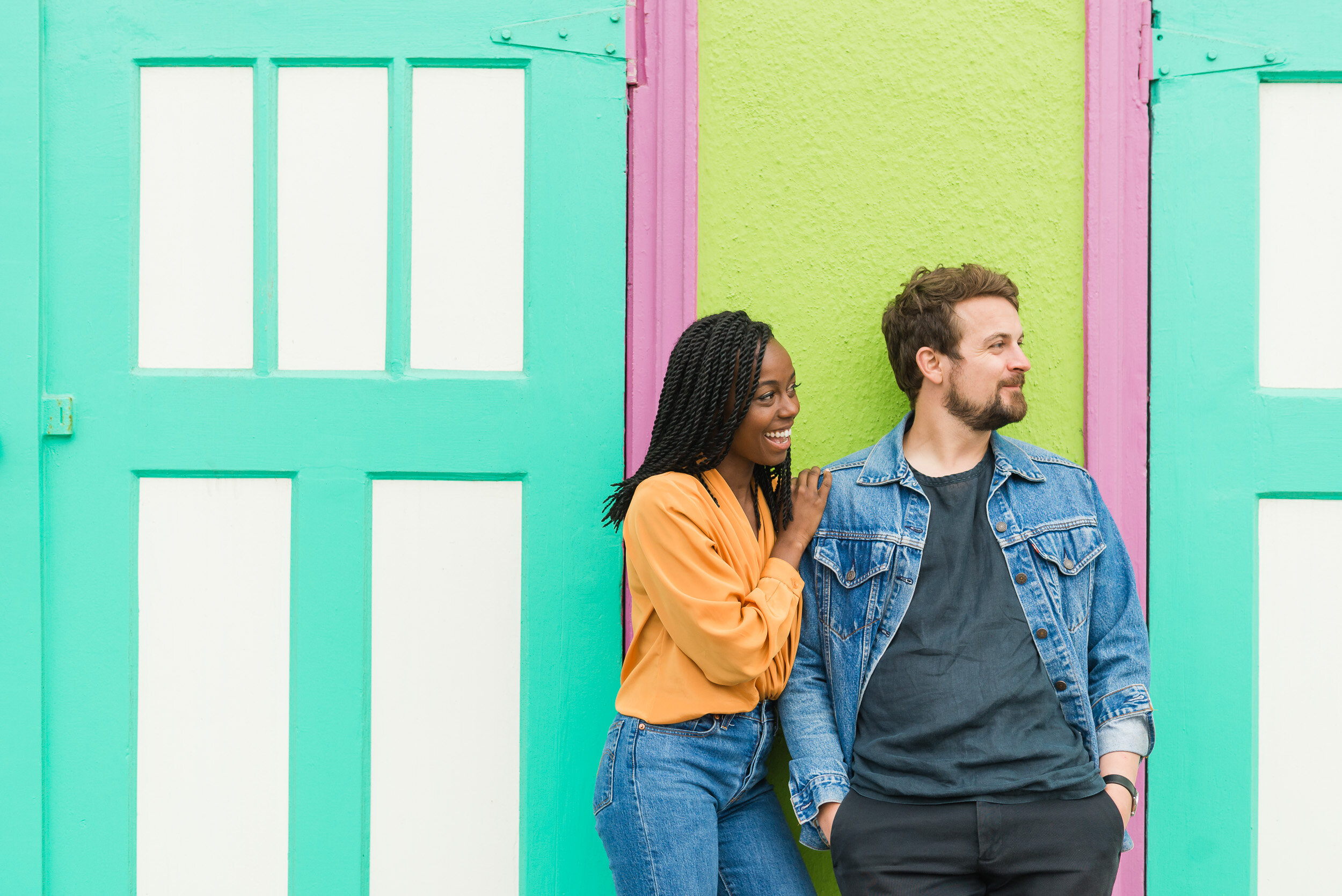 Engaged couple in front of a colorful wall in San Francisco's Outer Sunset neighborhood