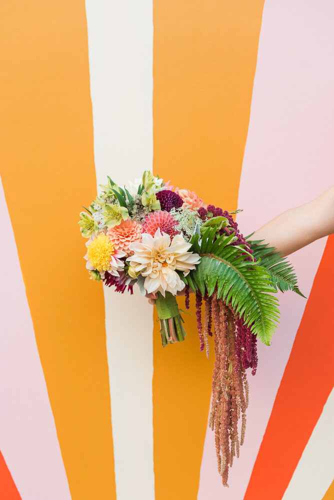 Bridal holding colorful bouquet in front of a mural